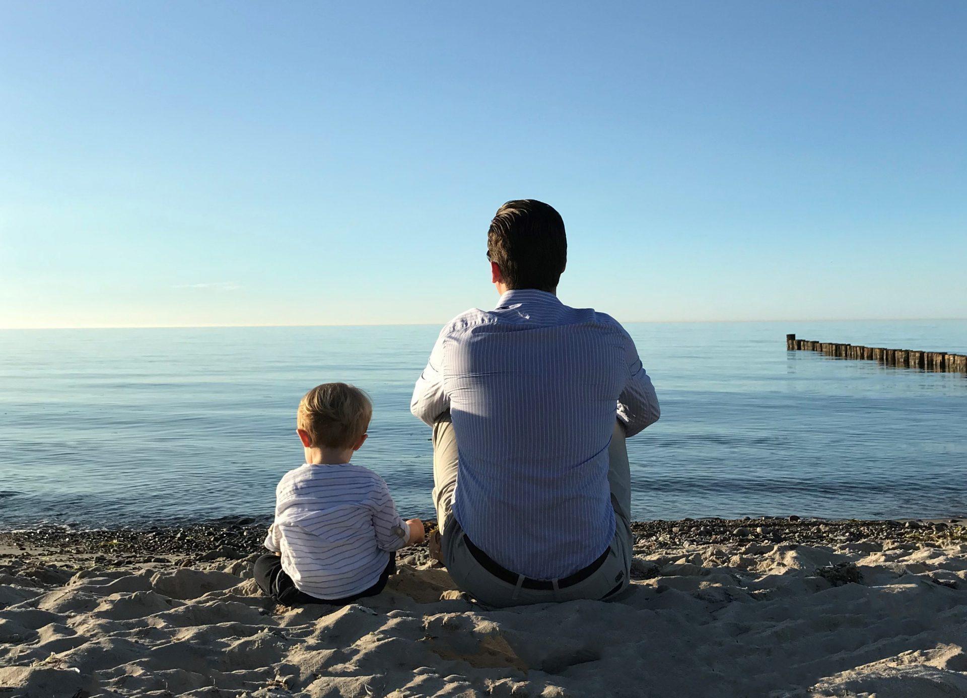 Vater und Sohn sitzen am Stand und schauen aufs Meer