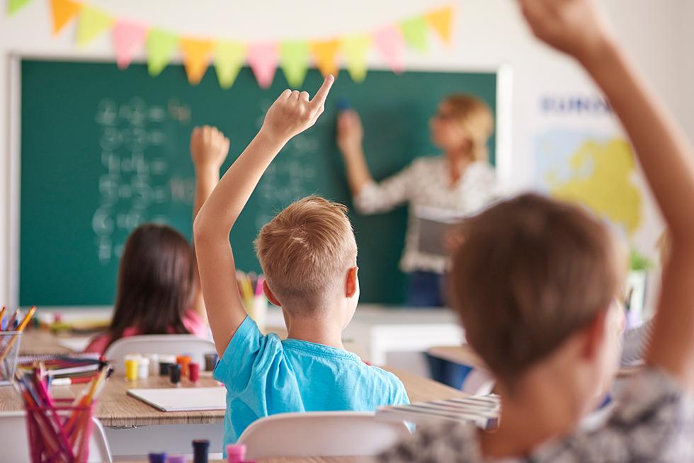 Kinder in Schule zeigen auf