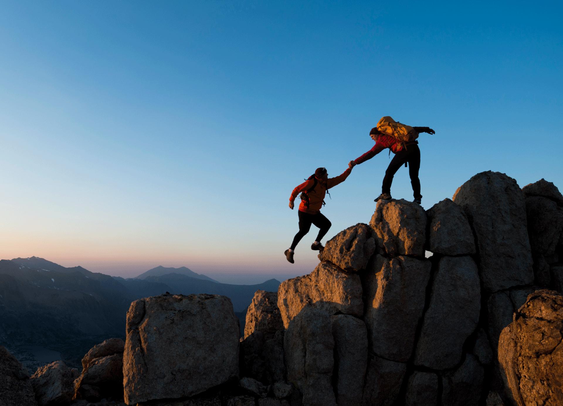 Ein Bergsteiger hilft einem anderem beim Aufstieg